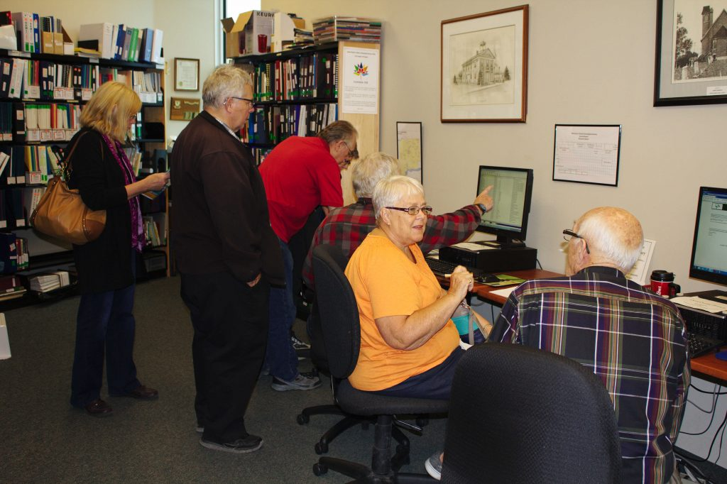 Terry, John and Patrick introducing guests to digital resources in the Genealogical Library